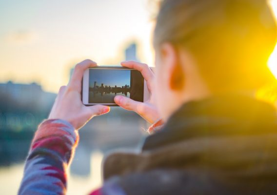 Young woman takes pictures of the city's panorama on a smartphone. City travel concept